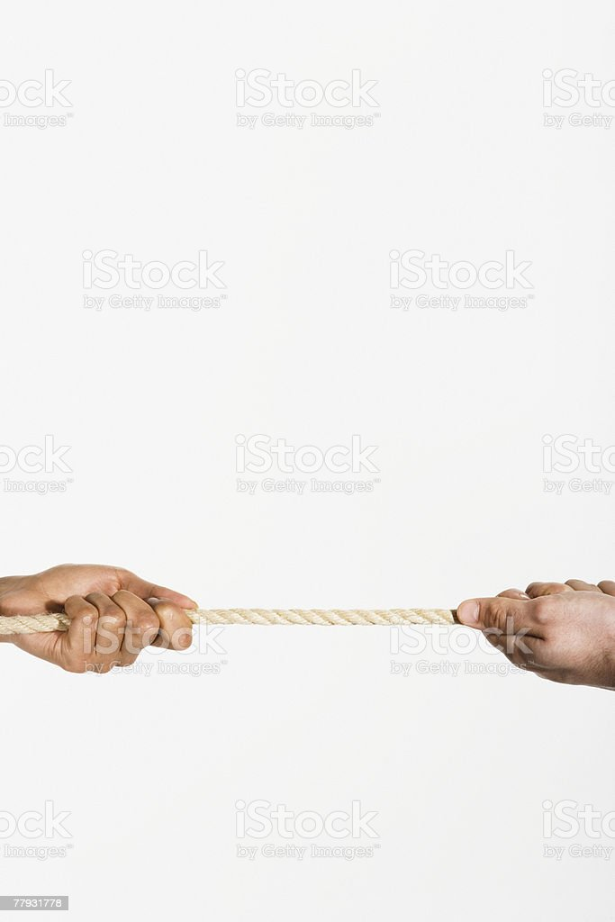 Two hands pulling opposite ends of a rope 免版稅 stock photo
