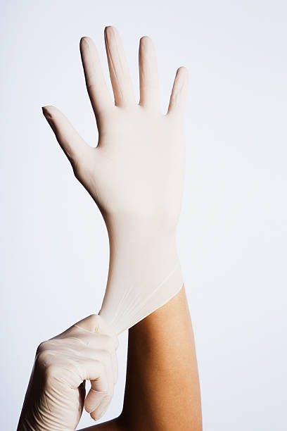 Two hands putting latex gloves on  surgical glove stock pictures, royalty-free photos & images