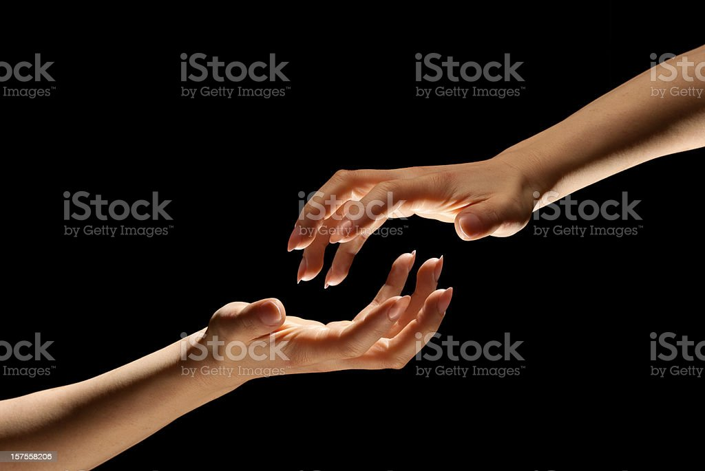 Two Hands Reach Out In Darkness to Hold One Another royalty-free stock photo