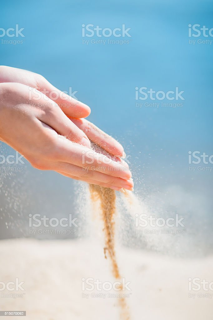 two hands sand through his fingers blue sky background stock photo