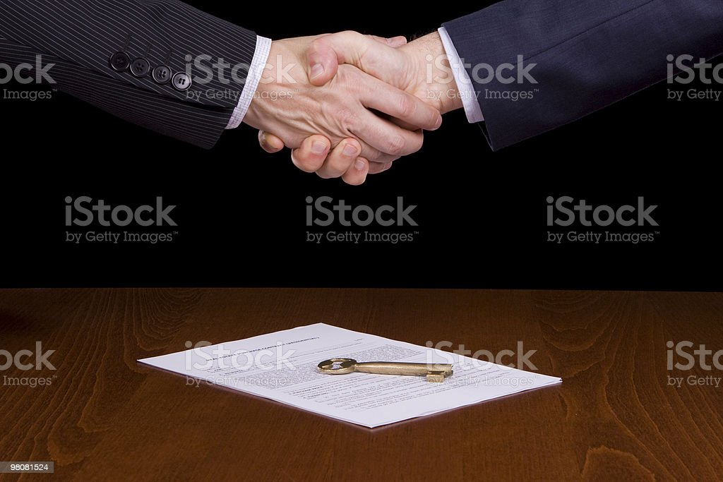 Two hands shaking over a contract and a key royalty-free stock photo