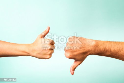 istock Two hands signalling thumbs up and thumbs down 176431462