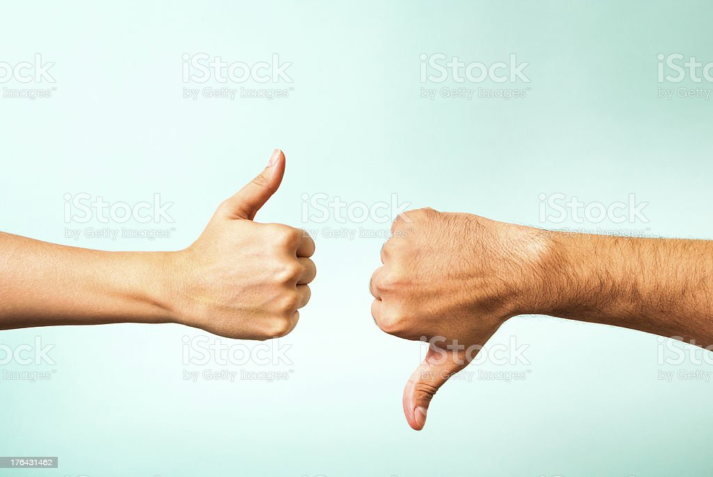 Two hands signalling thumbs up and thumbs down​​​ foto