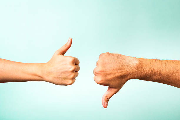 two hands signalling thumbs up and thumbs down - rudeness stock pictures, royalty-free photos & images