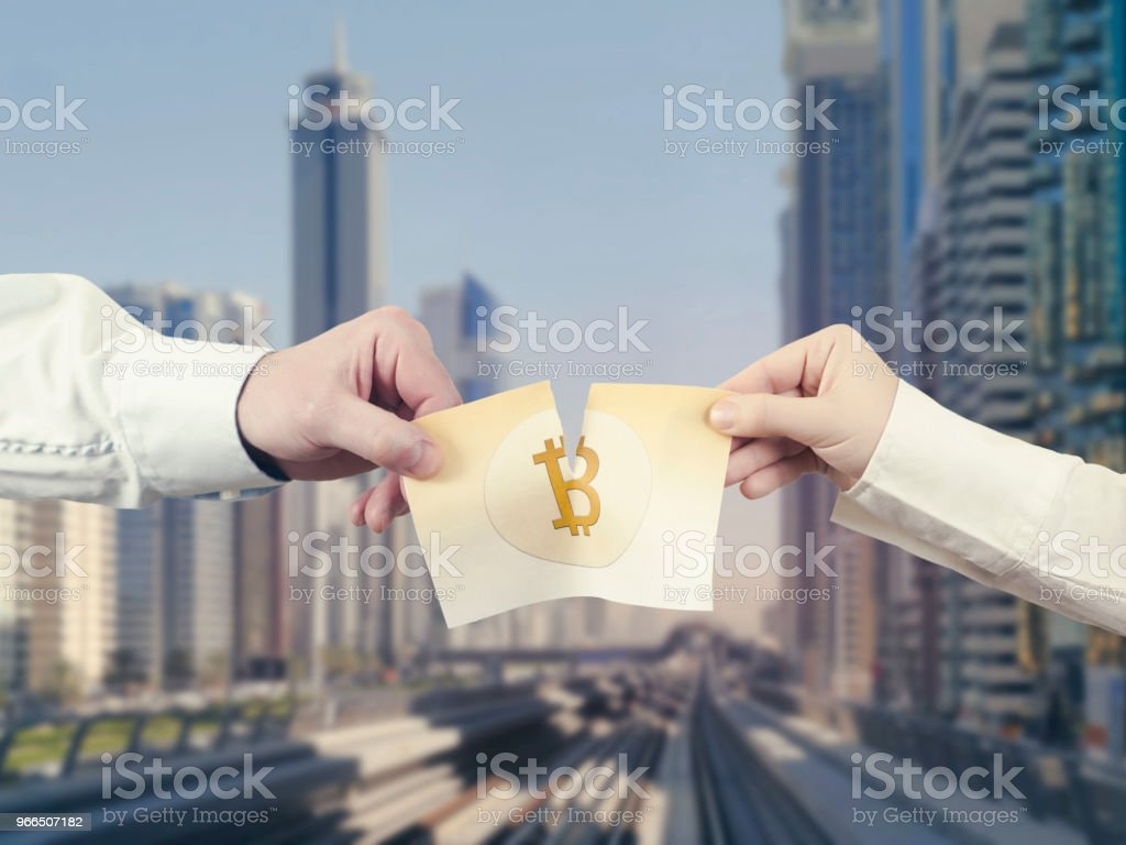 Two Hands Tear The Paper Banknote Of Bitcoin Into Two Part On The