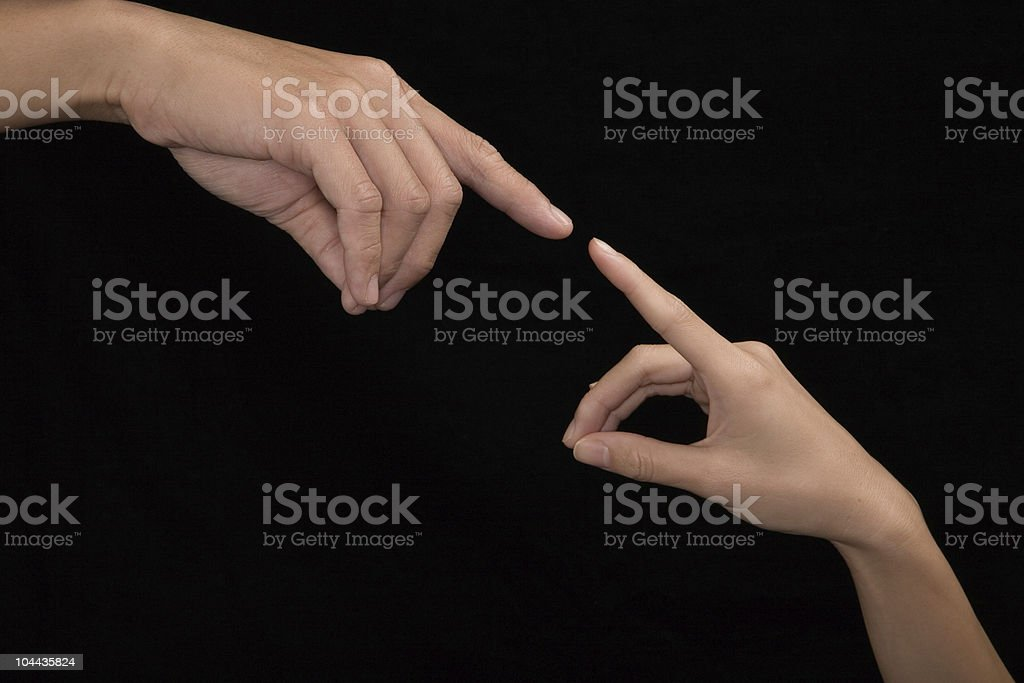 Two hands touching fingertips on black background stock photo