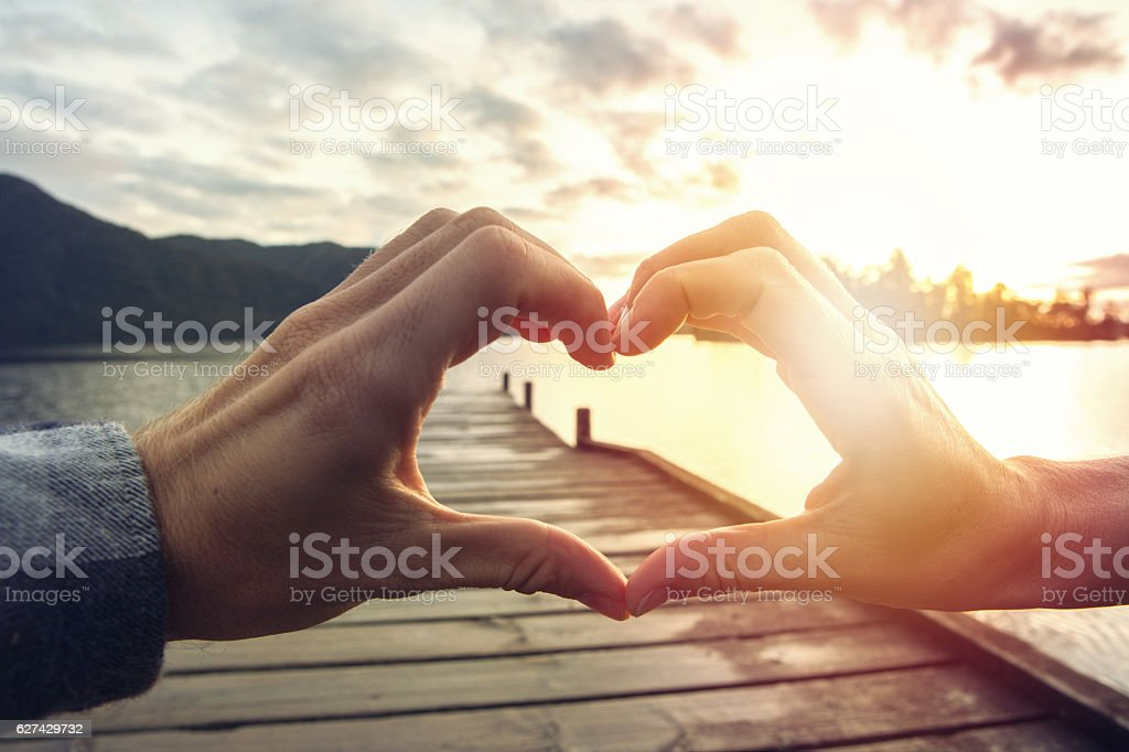 Two hands touching forms a heart shape finger frame stock photo