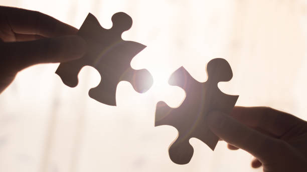 Two hands trying to connect couple wooden puzzle piece. Concept of association and connection, business strategy. stock photo