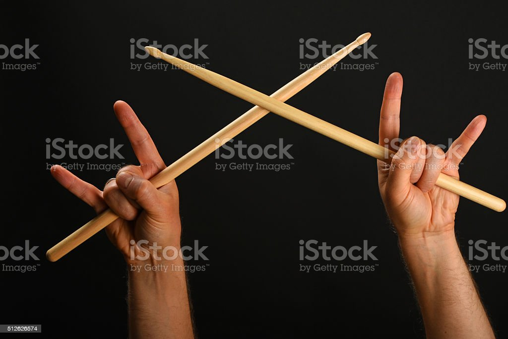 Two hands with crossed drumsticks and devil horns royalty free stockfoto