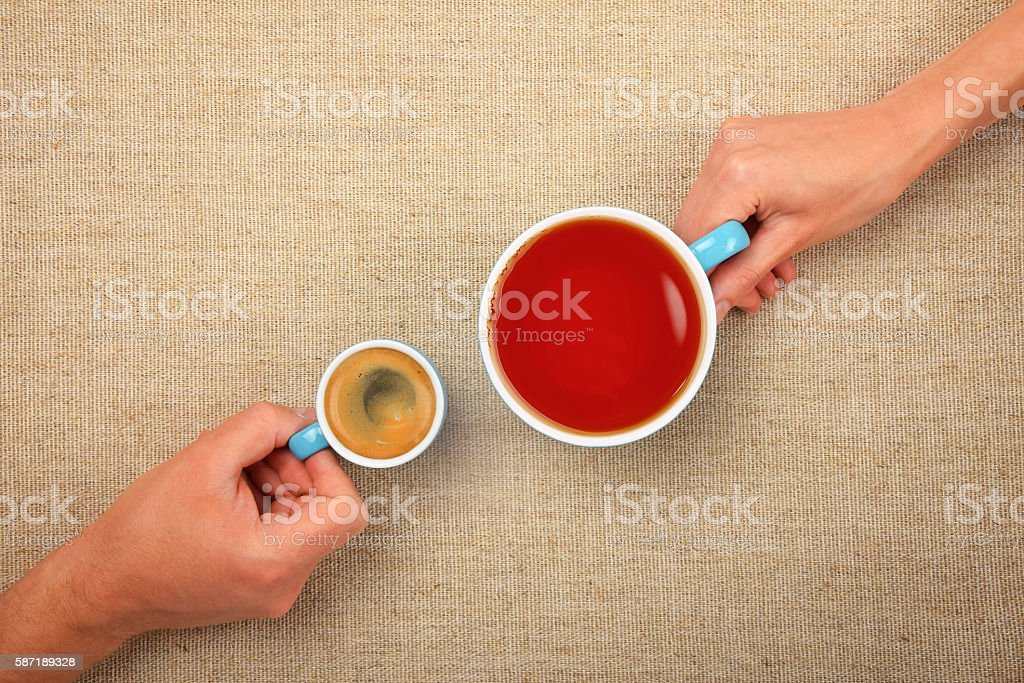 Two hands with espresso coffee and black tea cups stock photo