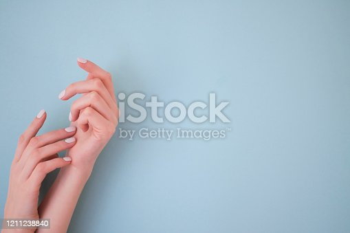 946930880 istock photo Two hands with manicure on blue background. 1211238840