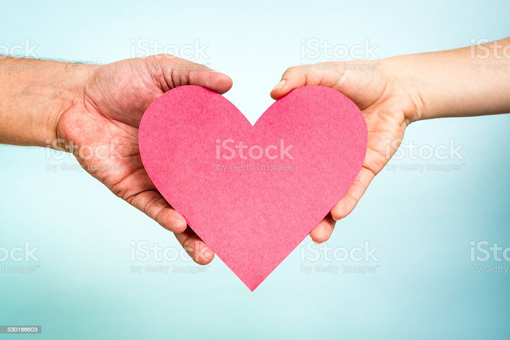 Two hands, woman man, showing red love heart, happy family stock photo