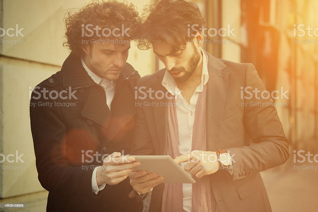 Two handsome businessmen watching on a digital tablet royalty-free stock photo