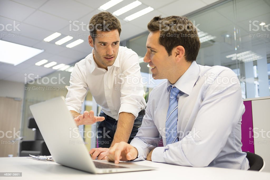Two handsome businessmen working together on computer stock photo