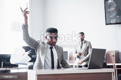 istock Two handsome cheerful african american businessman celebration successful with throwing paper in workplace 1135292111
