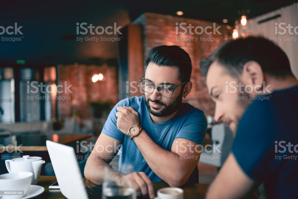 Two Handsome Friends Drinking Coffee and Surfing the Net In Cafe Restaurant stock photo