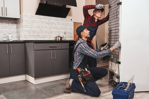 two handymen with refrigerator. young men mechanics checking refrigerator - household equipment stock pictures, royalty-free photos & images
