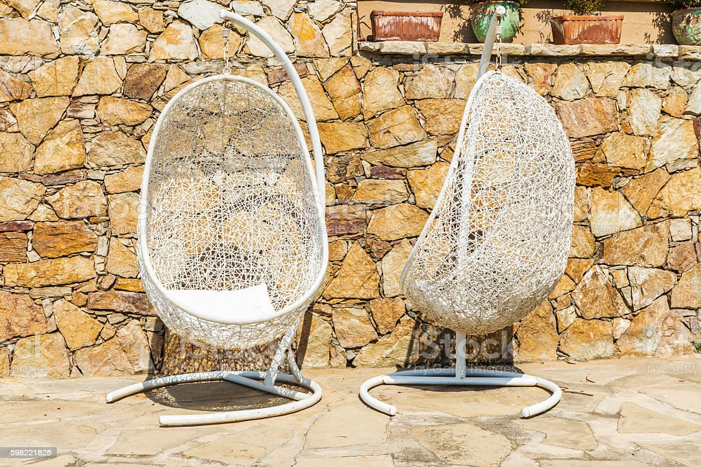 Two hanging chairs on the terrace foto royalty-free
