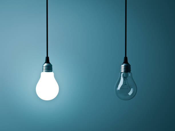 two hanging light bulbs , one glowing and one turned off on dark green blue background - contrasts stock pictures, royalty-free photos & images