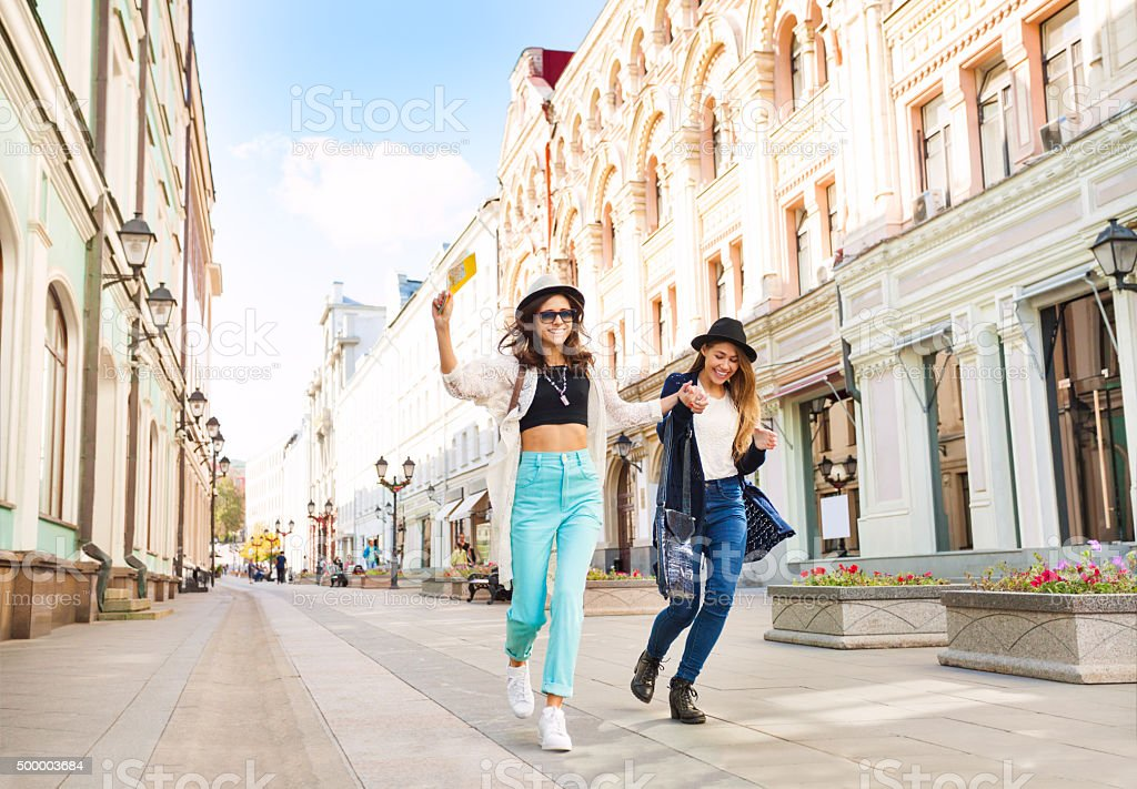 Two happily jumping girls while walking bildbanksfoto