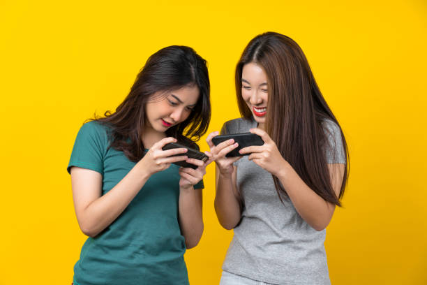 Two Happiness Asian smiling young woman gamer using smart mobile phone and playing games on isolated yellow color background Two Happiness Asian smiling young woman gamer using smart mobile phone and playing games on isolated yellow color background, Lifestyle and leisure with hobby concept gamers stock pictures, royalty-free photos & images