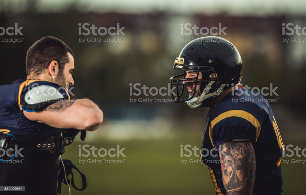 Two happy American football players talking on a field. royalty-free stock photo