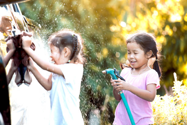 Two happy asian child girls having fun to help parent washing car together with sunlight stock photo