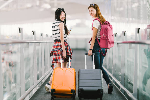 Two happy Asian girls traveling abroad together, carrying suitcase luggage in airport. Air travel or holiday vacation concept stock photo