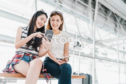 istock Two happy Asian girls using smartphone checking flight or online check-in at airport together, with luggage. Air travel, summer holiday, or mobile phone application technology concept 682572826