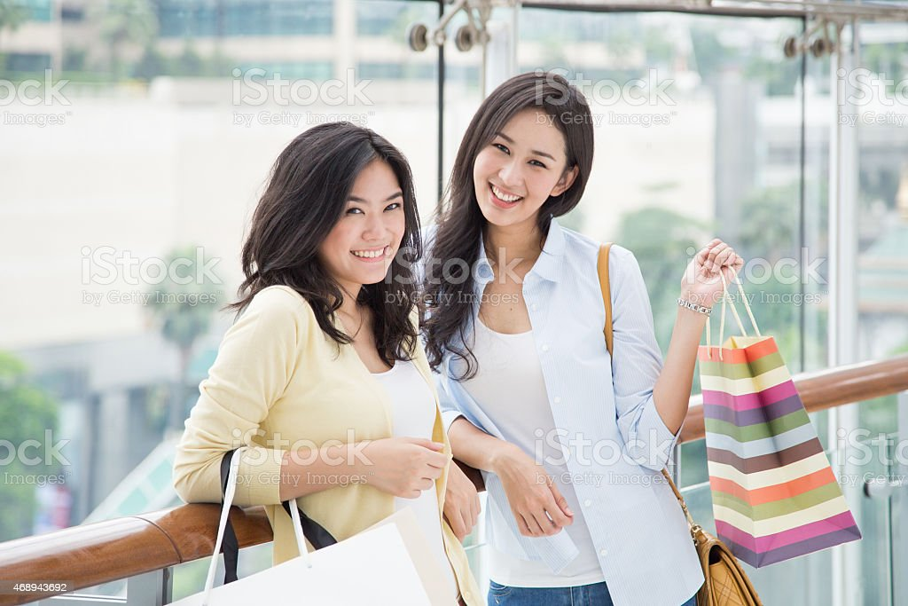 Two happy Asian women holding shopping bags stock photo