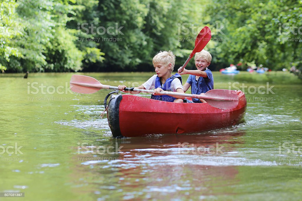 Two happy boys enjoying kayak on the river stock photo