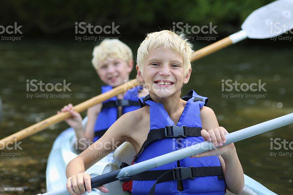Two happy boys enjoying kayak on the river stock photo