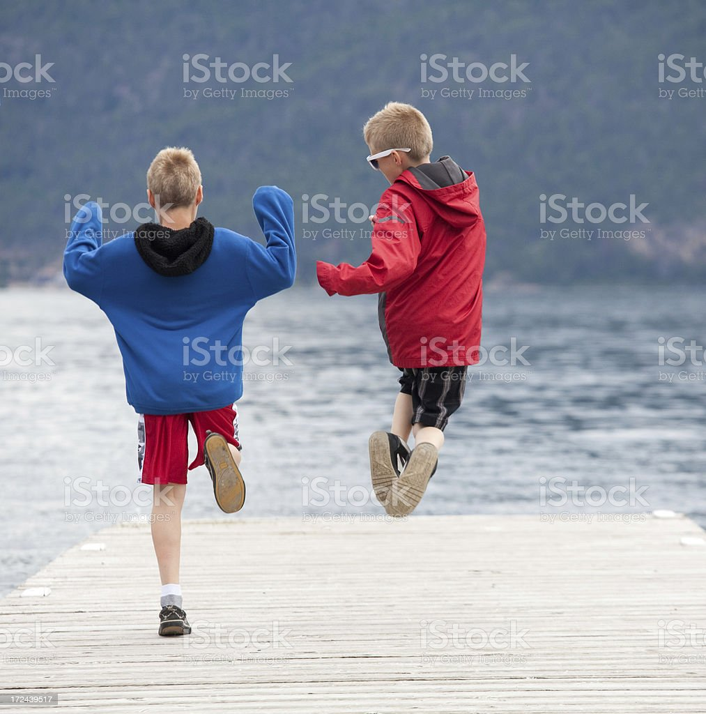 Two happy boys running and jumping on a dock royalty-free stock photo