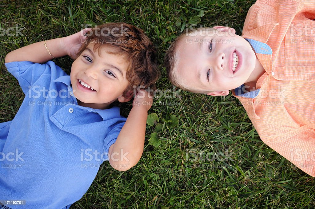 Two Happy Boys Smiling and Relaxing in the Grass royalty-free stock photo