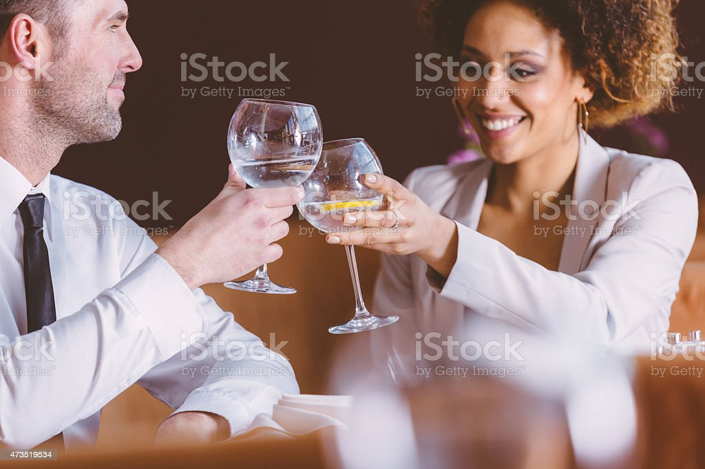 Two happy business people at lunch in the restaurant An afro american businesswoman and caucasian businessman having lunch or dinner in restaurant, sitting at the table, laughing and toasting with glass wine. 2015 Stock Photo