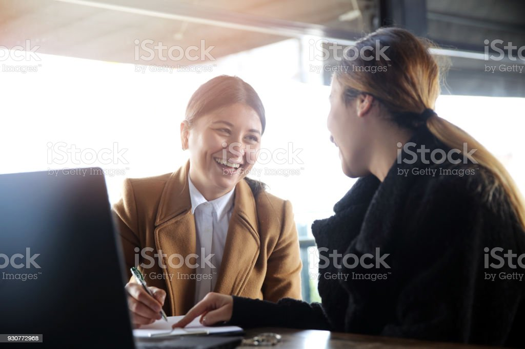 Two happy business woman talking stock photo