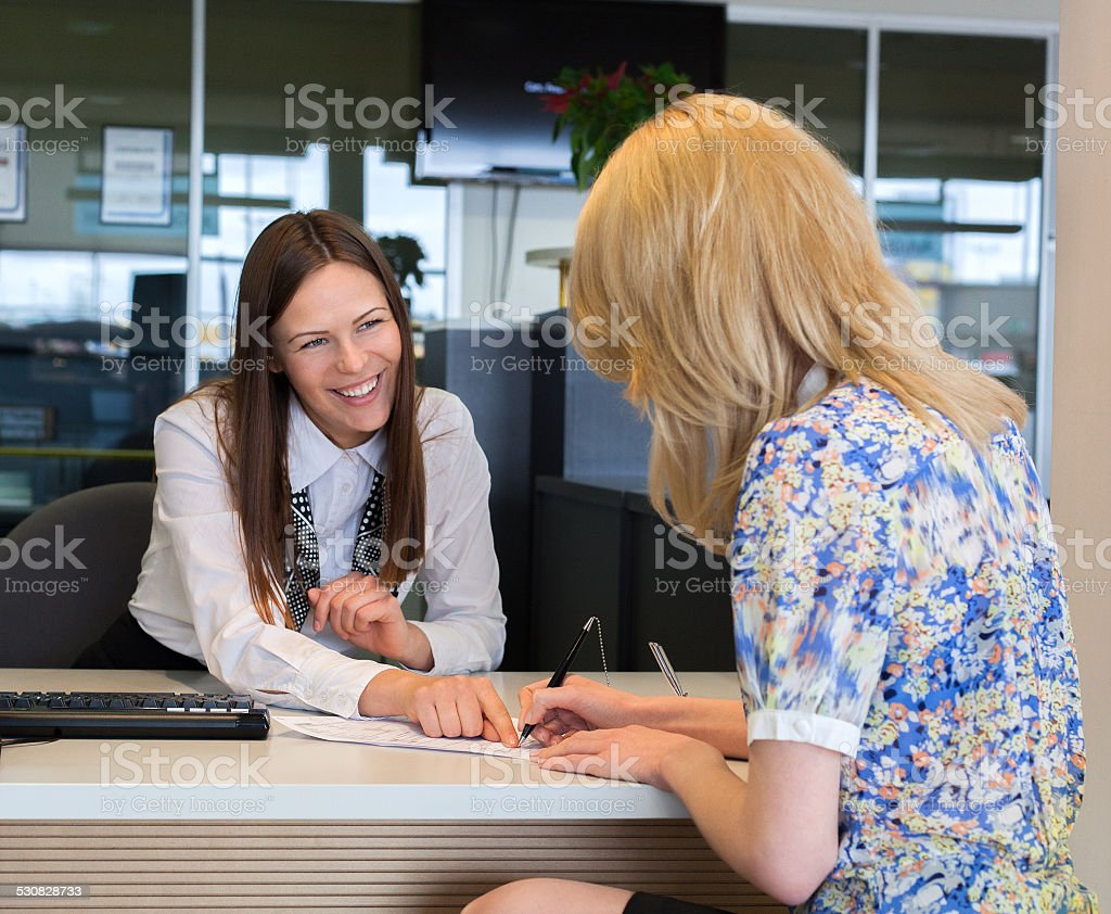 Two happy business women talking and signing credit or insurance stock photo