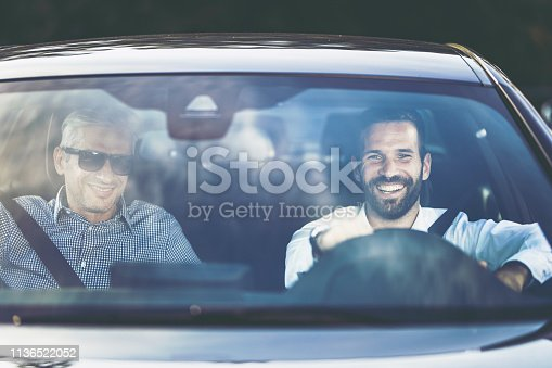 Happy business colleagues driving in a car while going on a journey. The view is though windshield.