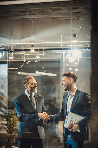 istock Two happy businessmen shaking hands in the office. 944318180