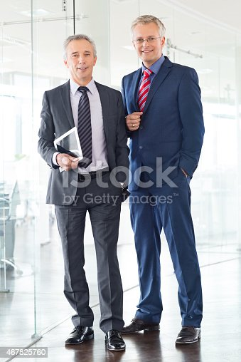 Full length portrait of two happy businessmen standing together in office and looking at camera