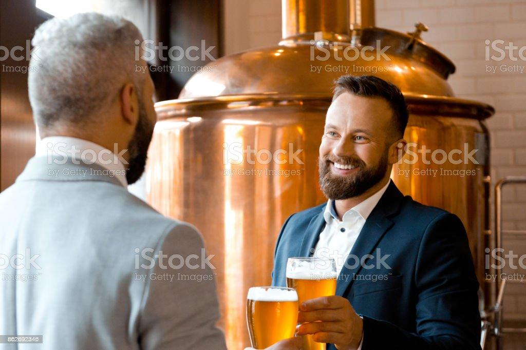 Two happy businessmen talking over beer in the microbrewery Two businessmen talking over beer in the microbrewery. Copper vat in the background. Adult Stock Photo