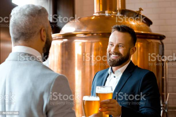 Two Happy Businessmen Talking Over Beer In The Microbrewery Stock Photo - Download Image Now
