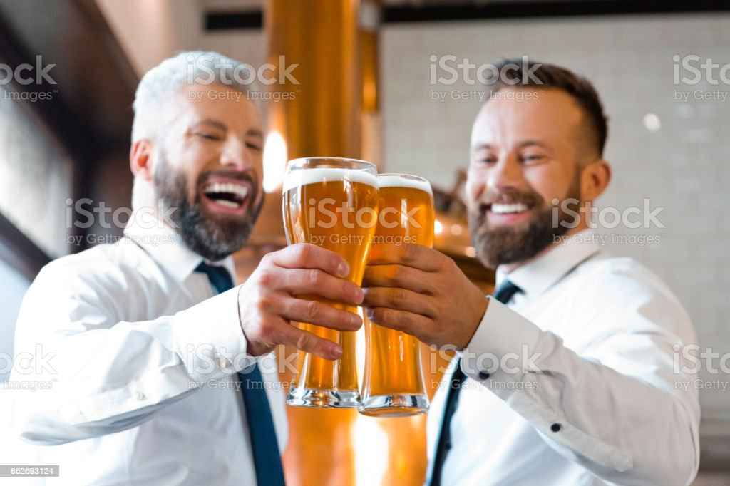 Two happy businessmen toasting with beer in the microbrewery Two businessmen wearing white shirt and ties toasting with beer in the microbrewery. Copper vat in the background. Adult Stock Photo