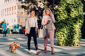 istock Two happy businesswoman walking down the street and talking 1207855278