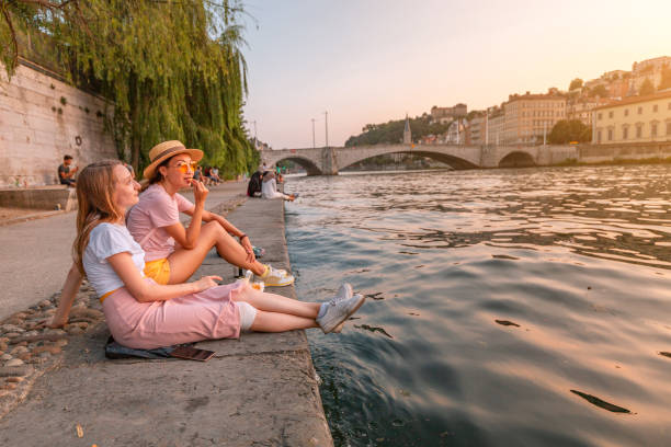 Two happy caucasian and asian girls friends meeting great sunset on a river Saone in Lyon city. Travel and lifestyle in France stock photo