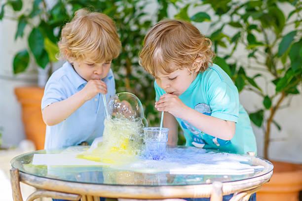 zwei glückliche kinder, die mit bunten blasen - versuche nicht zu lachen stock-fotos und bilder