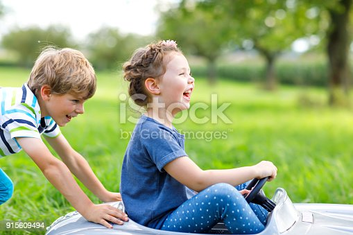 istock Two happy children playing with big old toy car in summer garden, outdoor 915609494