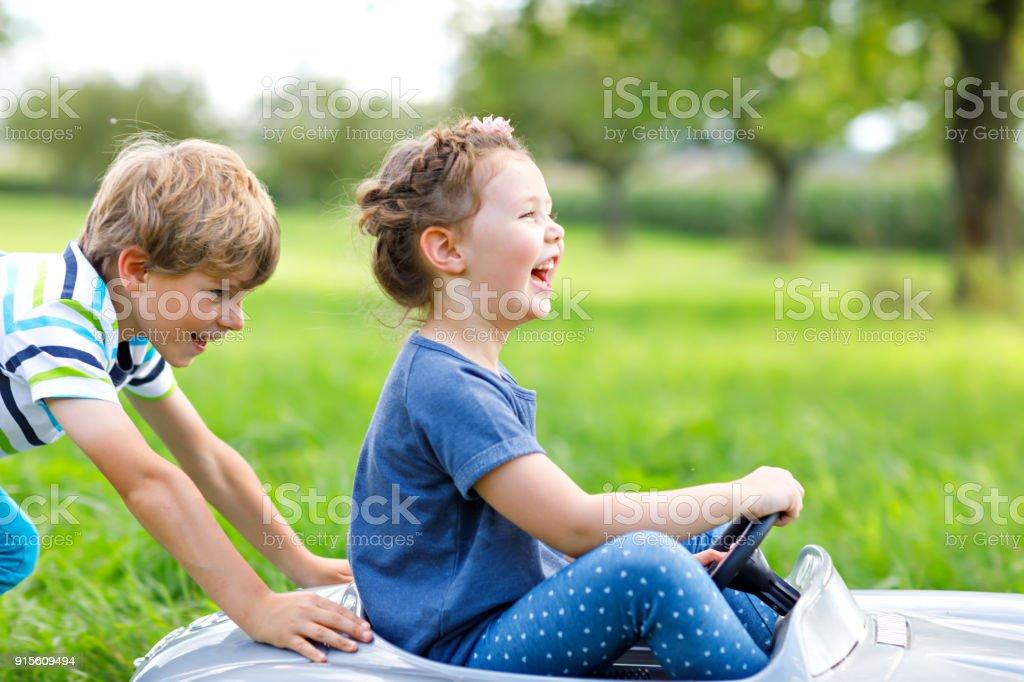 Zwei glückliche Kinder, die spielen mit großen alten Spielzeugauto im Sommergarten, im freien – Foto