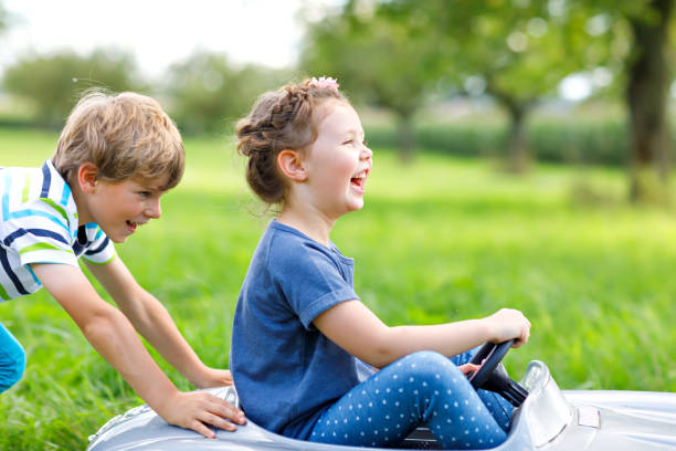 Two happy children playing with big old toy car in summer garden, outdoor stock photo