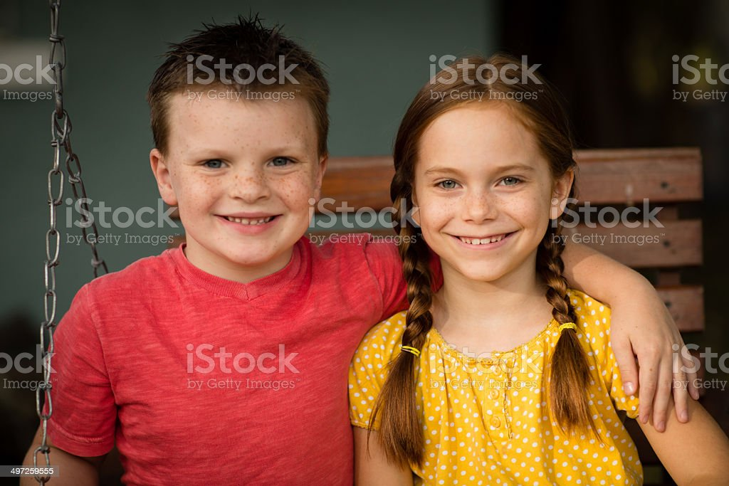 Two  Happy Children Sitting on Swing Outdoors royalty-free stock photo